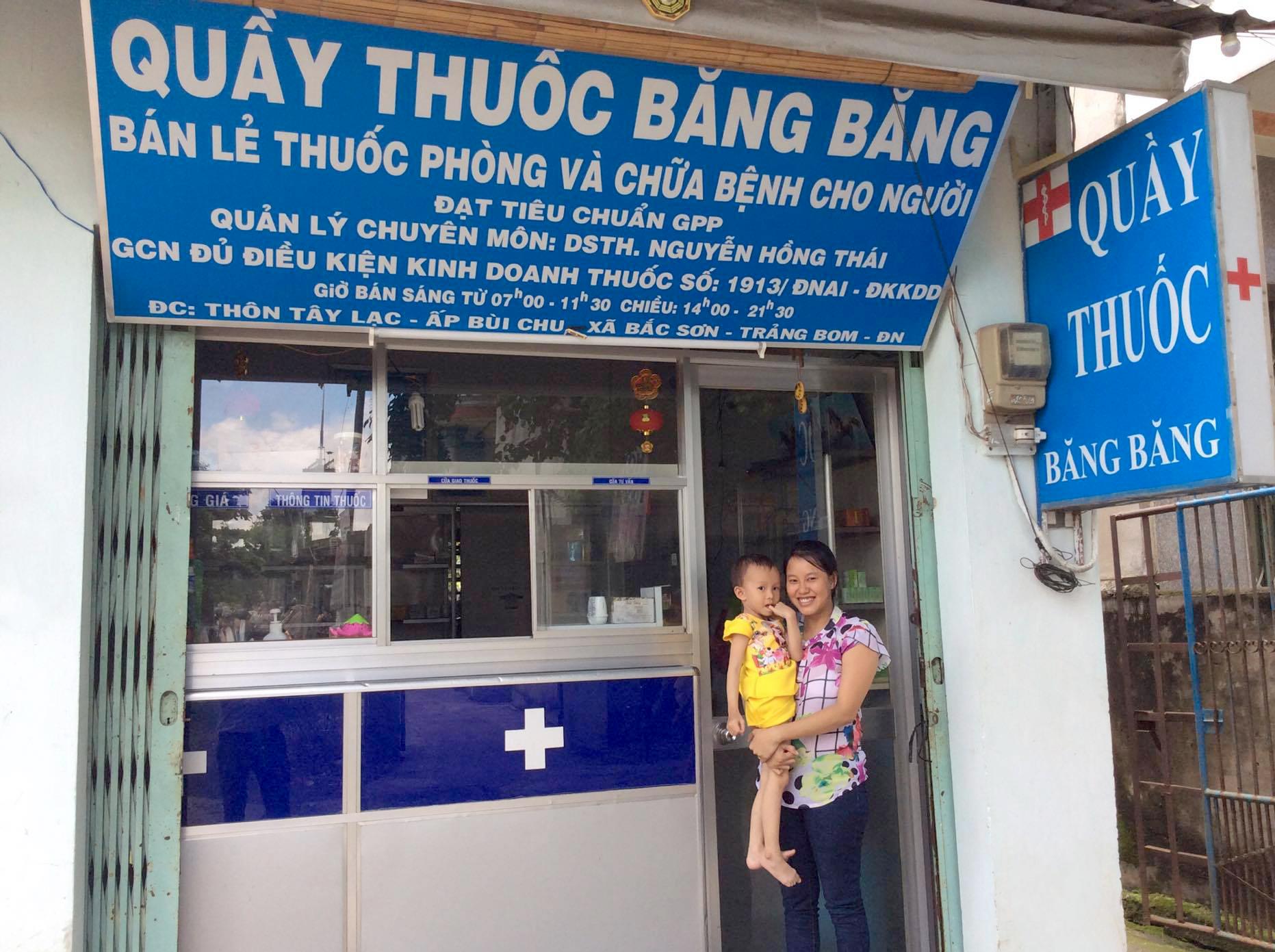 Bé Băng Băng và mẹ tươi tắn tại quầy thuốc của chị Phương (Ảnh: Như Quỳnh)